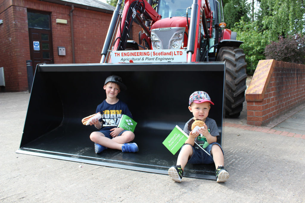 Two young boys eating food in a tractor shovel