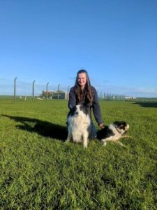 Student Rhona Earnshaw sitting with her two sheep dogs on her farm on a clear sunny day